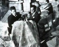 Two men in a warehouse looking at quilts Shelly Zegart Archives