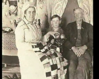 Historic photograph of a man, woman and child with a quilt In upcoming book by Janet E. Finley, Schiffer Publishing, Atglen, Pennsylvania; late 2012 Collection of Janet E. Finley