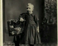 Historic photograph of a child leaning on a quilt  draped over a table Shelly Zegart Archives