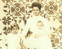 Historic photograph of a mother and her two children in  front of a quilt  In upcoming book by Janet E. Finley Schiffer Publishing, Atglen, Pennsylvania; late 2012 Collection of Janet E. Finley
