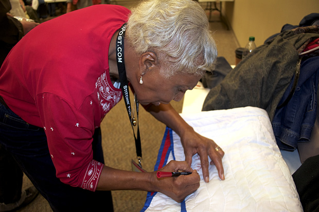 """Lucy Mingo signing the """"Bible Story"""" quilt, 2011"""