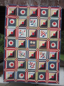 Round and assorted log cabin quilt by Jack Edson